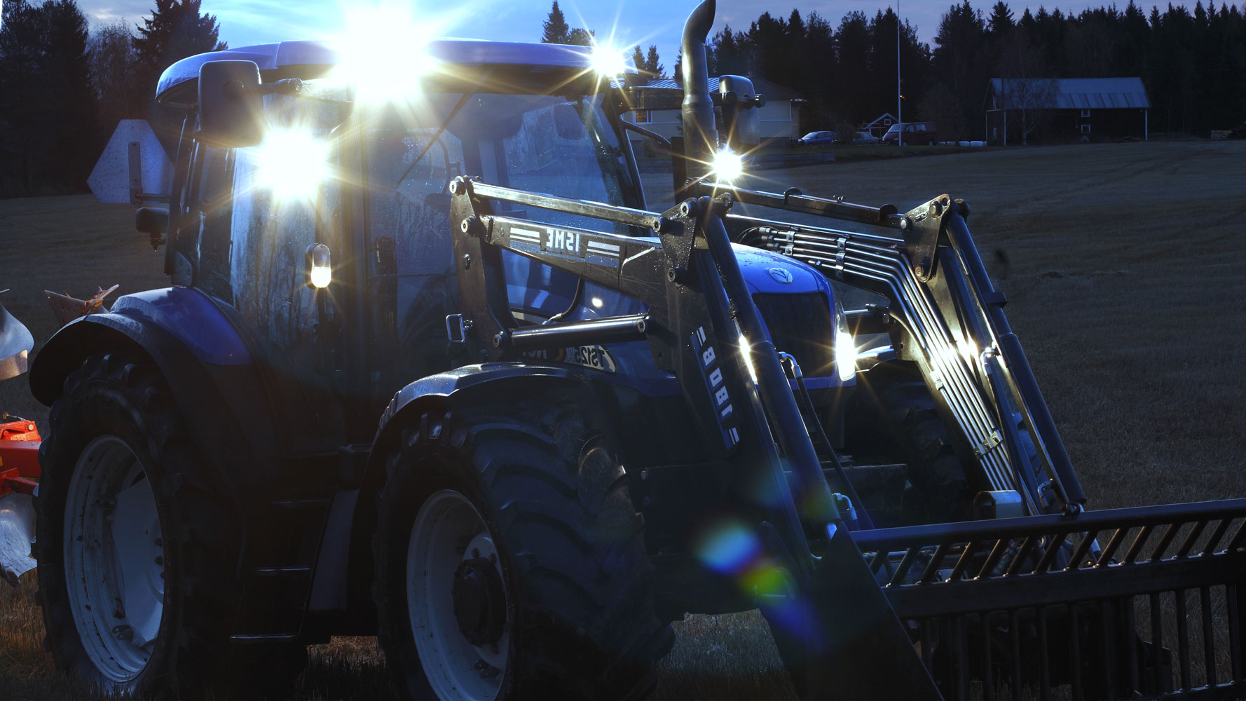 Nordic Lights LED tractor lights mounted on blue tractor working on field