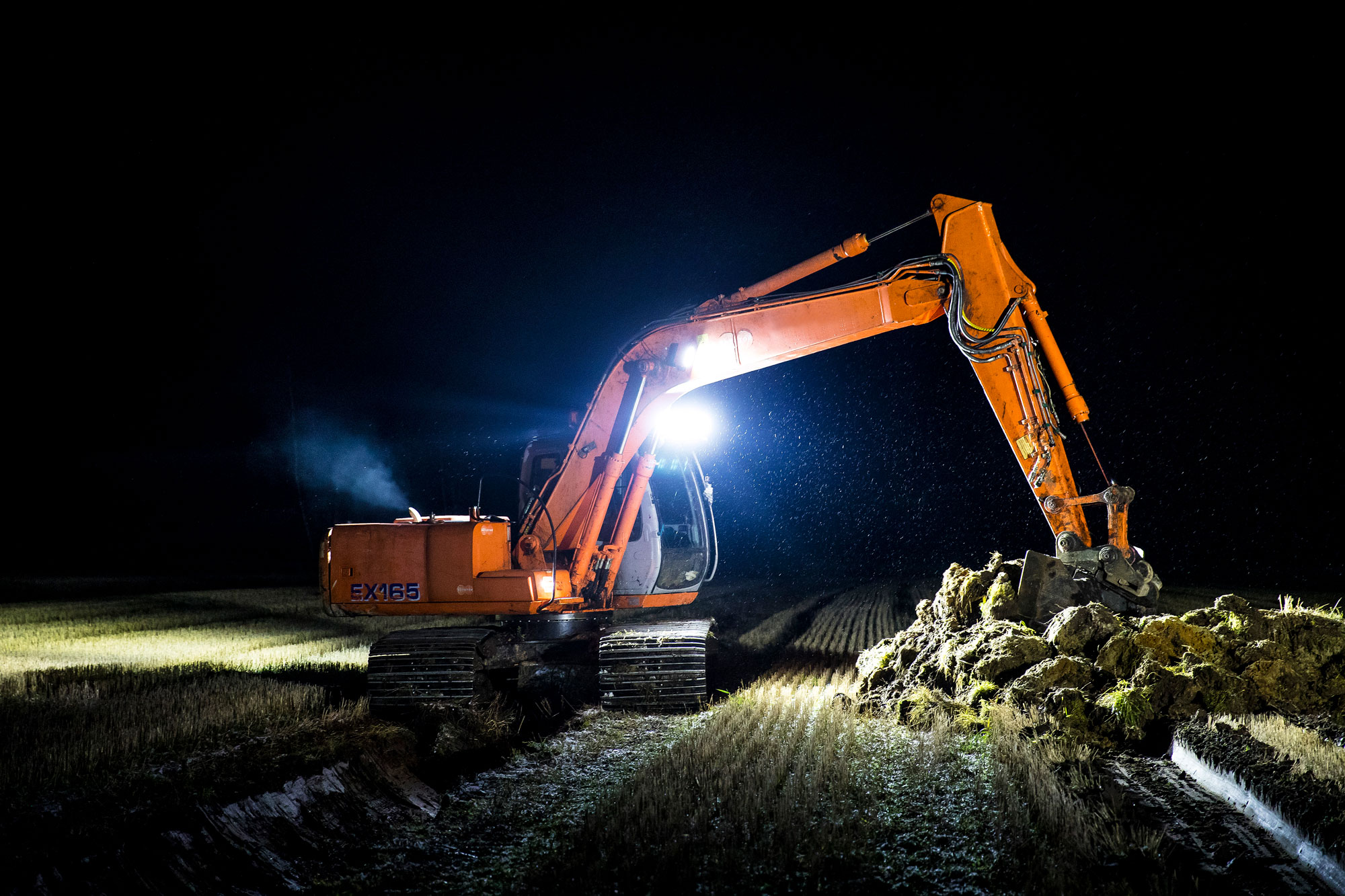 Orange excavator digging with Nordic Lights LED Lights
